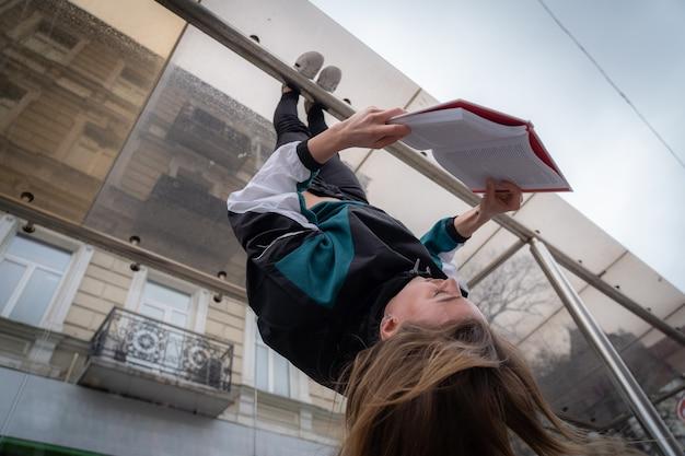 Девушка висит за ноги вверх ногами на улице и читает книгу концепции образования и саморазвития ...
