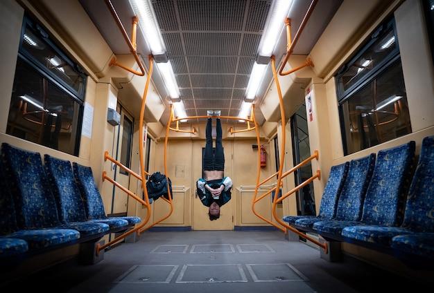 Девушка висит вверх ногами в вагоне метро и использует смартфон. концепция чрезмерного использования социальных сетей и зависимости. Premium Фотографии