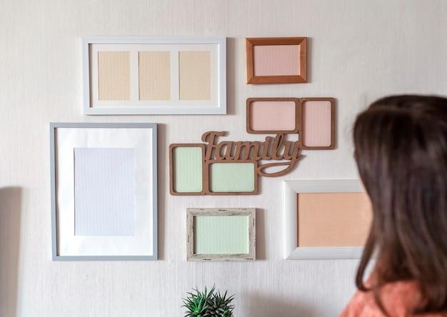 가족 사진 갤러리를 만들기 위해 다른 빈 세로 및 가로 그림 프레임 세트로 흰 벽에 프레임을 걸려있는 소녀, 흰 벽에 모형 템플릿, 라이프 스타일