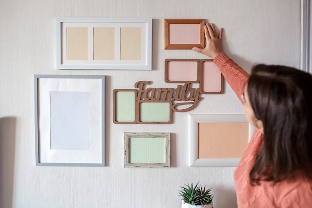 Girl hanging frame on white wall with set of different empty vertical and horizontal picture frames to create family photo gallery, to capture a moment, mockup template on white wall, lifestyle