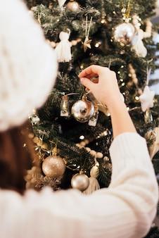 소녀는 크리스마스에 새해 장식을 걸어 놓습니다.