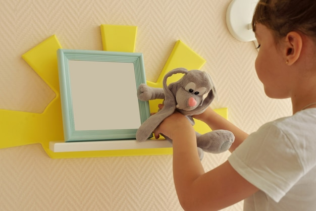 Girl happy lifestyle puts a gray hare on a shelf in the form of a yellow sun. children's shelves in the form of white clouds on a plain beige wall. trendy shelves in the room.