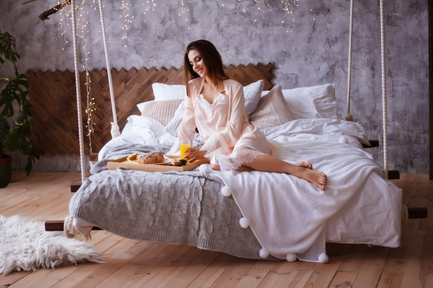 女の子はベッドで朝食を持っています