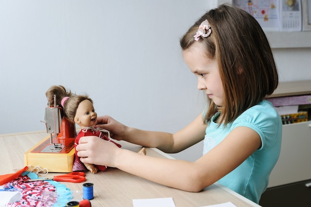 The girl has sewn a new dress and dressed it on a doll.
