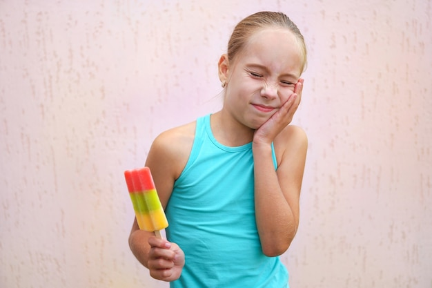 Girl has toothache from cold ice cream.