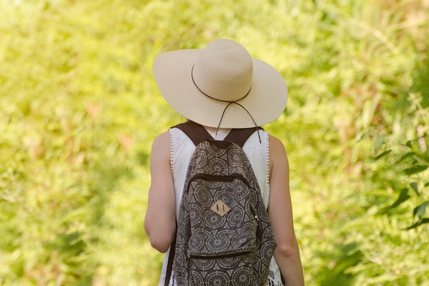 Girl in a hat and a backpack stands in a park. back view
