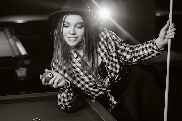 A girl in a hat in a billiard club with a cue and balls in her hands.playing pool. black and white photo.