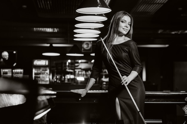 A girl in a hat in a billiard club with a cue in her hands.billiards game.black and white photo.