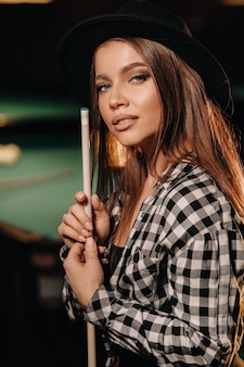 A girl in a hat in a billiard club with a cue in her hands.pool game.