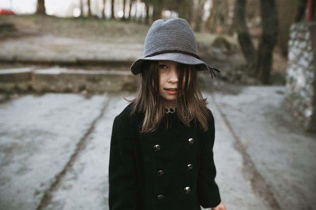 Girl in hat and coat posing outside