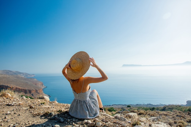 Girl in hat and dress with sea coastline