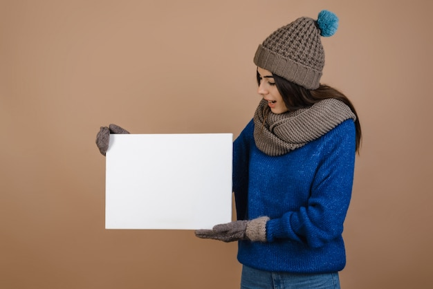 Girl in hat and gloves holding white blank poster. isolated on brown background.