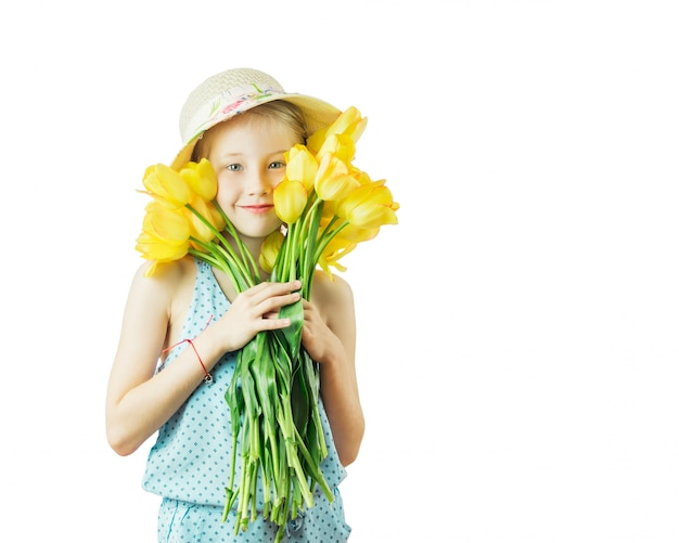 Girl in hat hugging a bouquet of yellow tulips isolated on a white background.