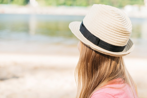 Girl in hat looking at water