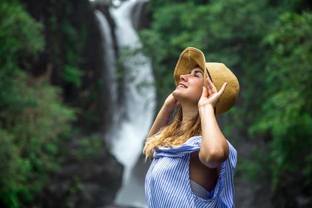 Ragazza con cappello guardando la cascata