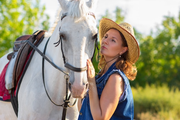 The girl in a hat looks at a horse and irons it on a muzzle