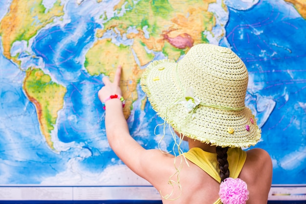 Girl in a hat points to a world map with a finger