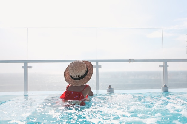 A girl in a hat in the pool looks at the sea. summer background with place for text.