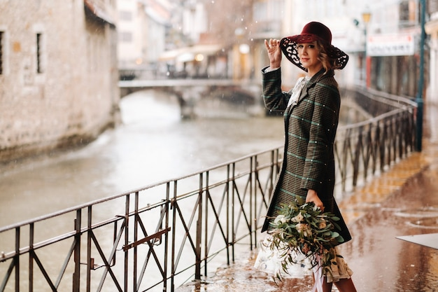A girl in a hat in rainy weather in the old town of annecy. france.a woman's walk around the city in rainy weather.