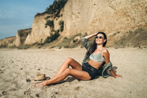 Girl in hat relaxing on the beach with rocks on background