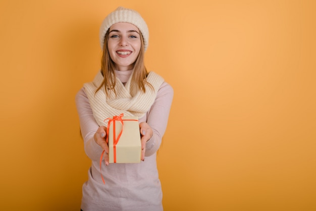 The girl in a hat and scarf gives a gift