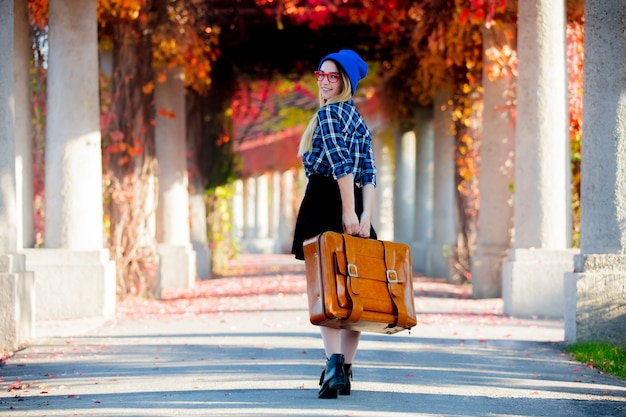 Girl in hat and shirt with suitcase in red grape alley