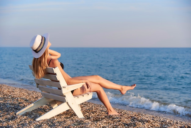 A girl in a hat sits on a chair by the sea.