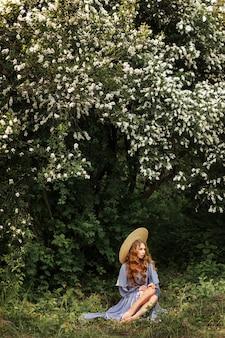 Girl in hat sits under flowering tree in summer