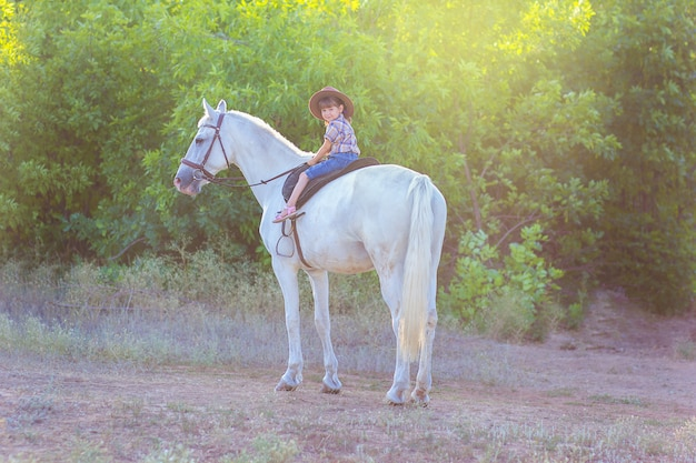 The girl in a hat sits on a horse