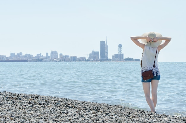 Girl in a hat stand along the seashore. city in the distance. back view