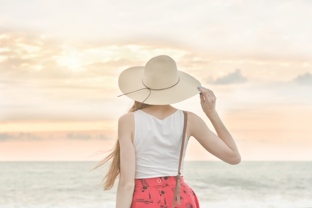Girl in a hat stand by the sea, sunset. back view
