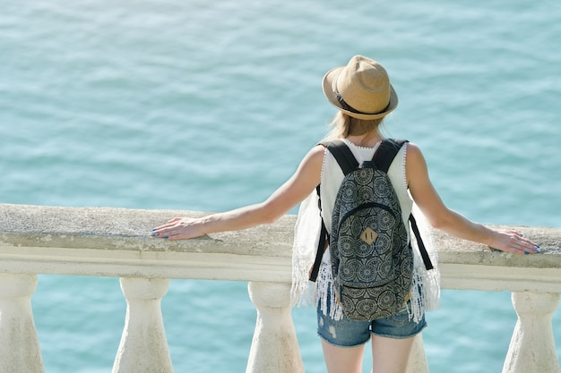 Girl in hat standing on the balcony and looking at the sea. back view