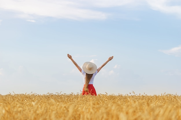Girl in hat stands in middle of wheat field raising his hands to sky