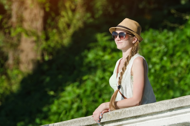 Girl in a hat and sunglasses enjoying nature. sunny day, park