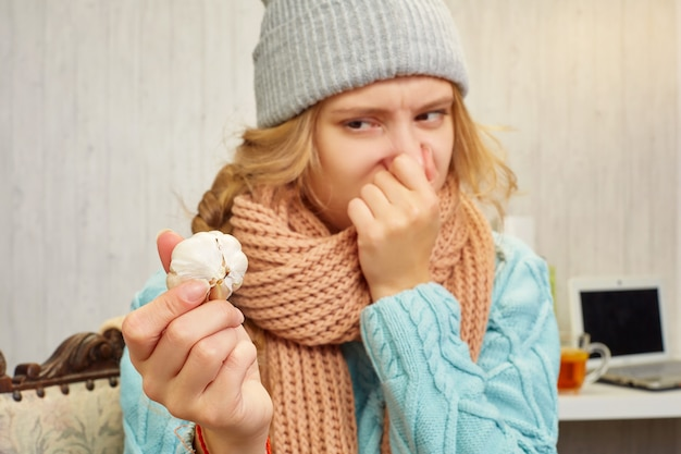 A girl in a hat, sweater and scarf holds a head of garlic at arm's length holding her nose with the other hand