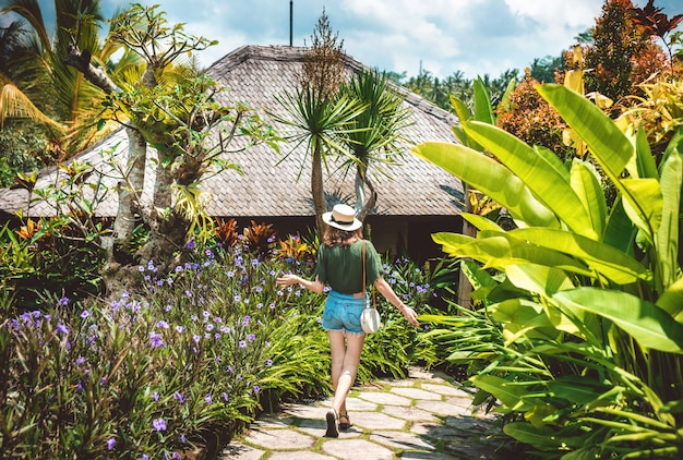 A girl in a hat walks on a sunny day through the territory of a luxury hotel in ubud.a young woman walks along a path surrounded by bright flowers and tropical plants, view from the back, bali, ubud.