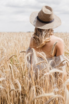 Girl in a hat in a wheat field in summer. back view