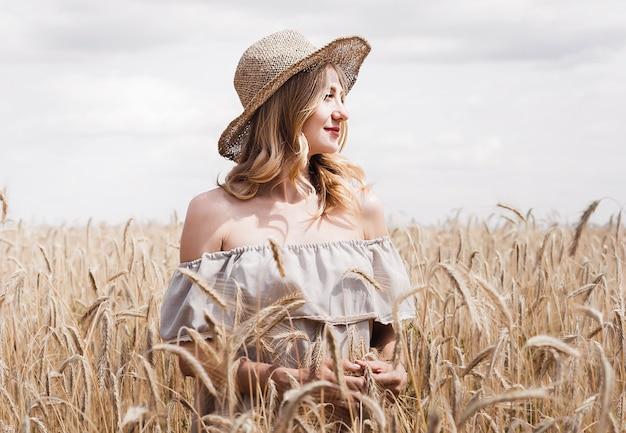 Girl in a hat in a wheat field in summer
