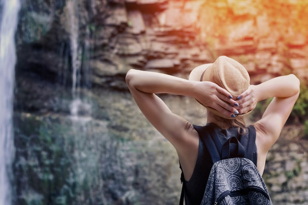 Girl in a hat with backpack looking at a waterfall.