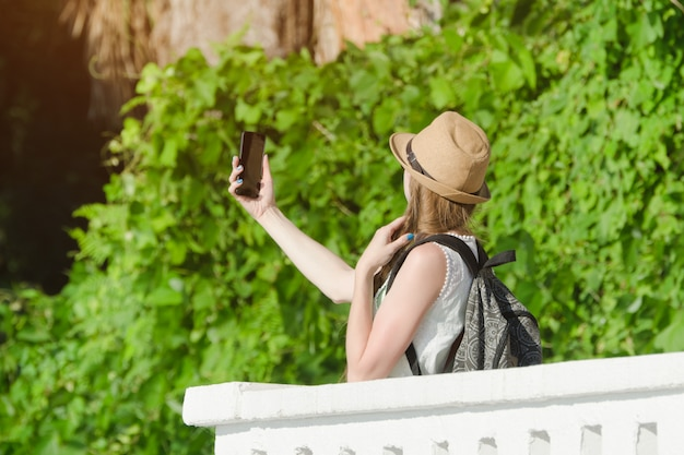 Girl in a hat and with a backpack makes selfie in the park