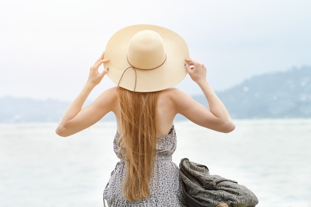 Girl in a hat with a backpack sitting on the pier. mountains on the background. view from the back