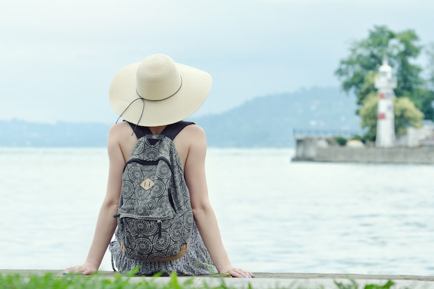 Girl in a hat with a backpack sitting on the pier. mountains and lighthouse on the background.