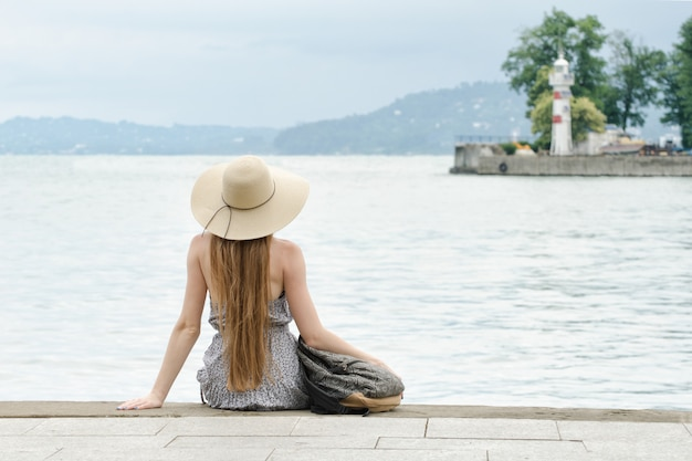 Girl in a hat with a backpack sitting on the pier. mountains and lighthouse on the . view from the back