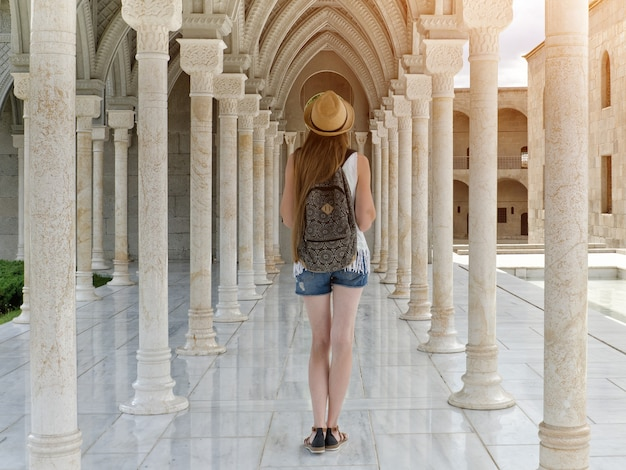 Girl in a hat with a backpack standing among columns. back view