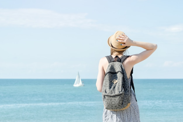 Girl in a hat with a backpack standing on the coastline. sailboat in the distance. back view