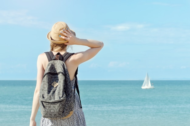 Girl in a hat with a backpack standing on the coastline. sailboat in the distance. view from the back