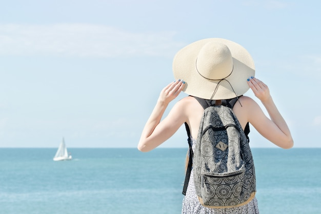 Girl in a hat with a backpack standing on the coastline.