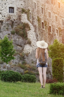 Girl in a hat with a backpack standing near the fortress. back view