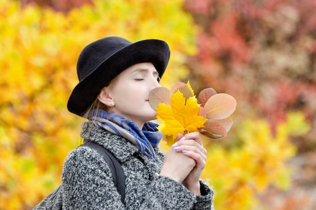 Girl in a hat with a bouquet of autumn leaves.