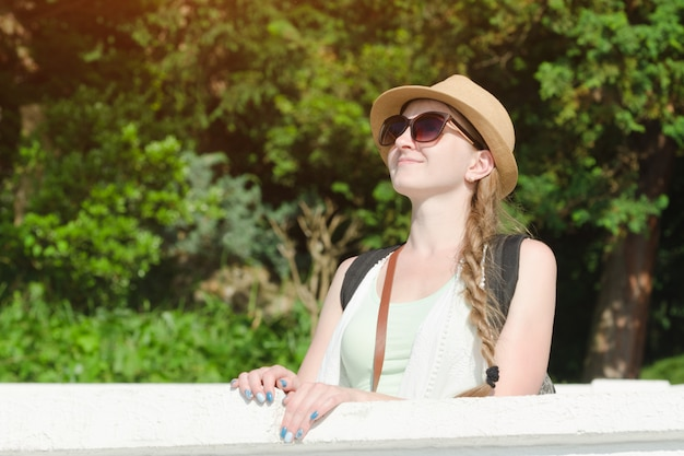 Girl in a hat with sunglasses enjoying nature. sunny day, park